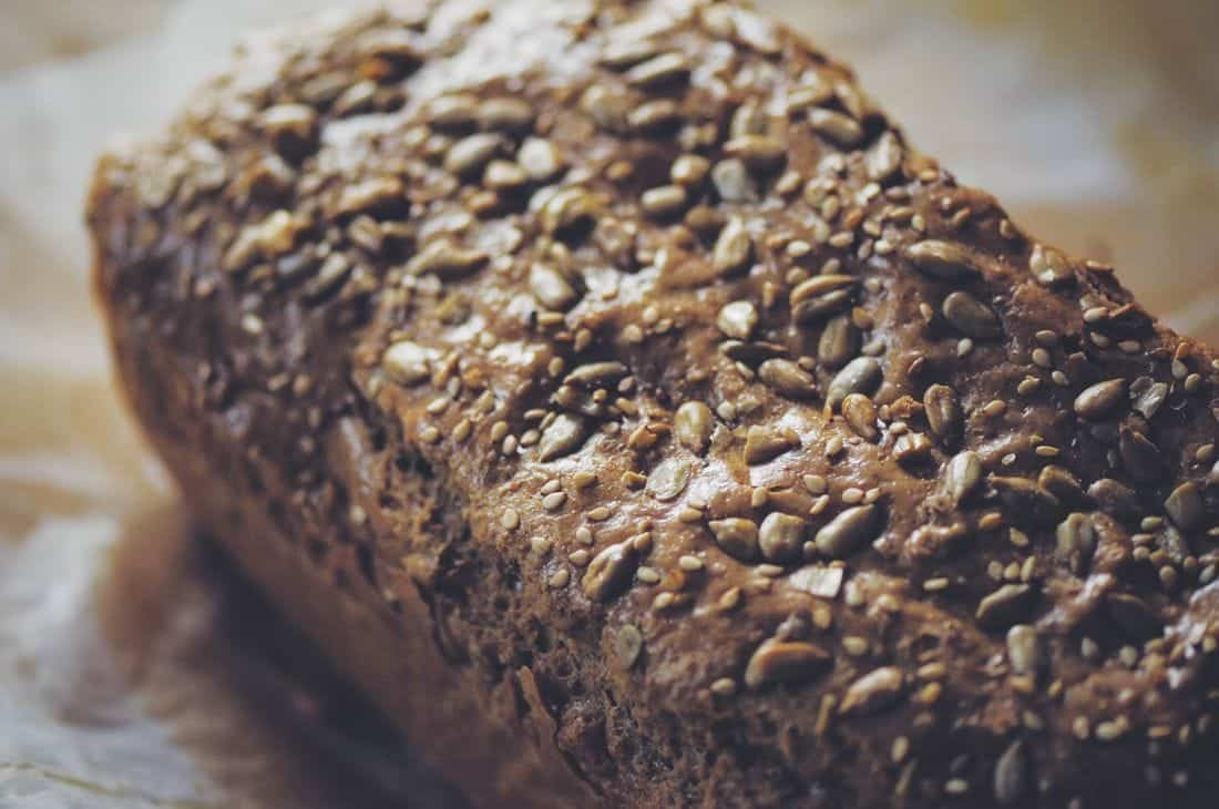 a close up of a loaf of tahini bread covered in seeds