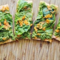 slices of red lentil pizza arranged on a wooden cutting board topped with pesto