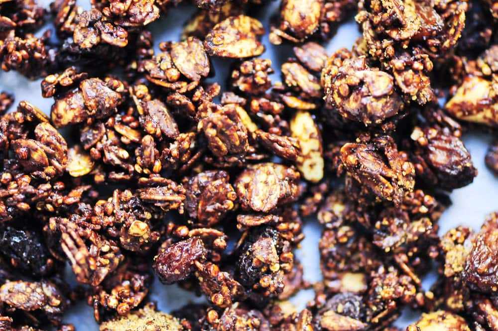 A crunchy gluten-free & vegan quinoa granola with oats, raisins, peanuts, cocoa and a hint of ginger. High in iron, protein and B vitamins! It makes a great breakfast or snack! #quinoagranola #chocolategranola #molasses #glutenfreegranola #crunchy #cereal #vegangranola #breakfast #healthysnack