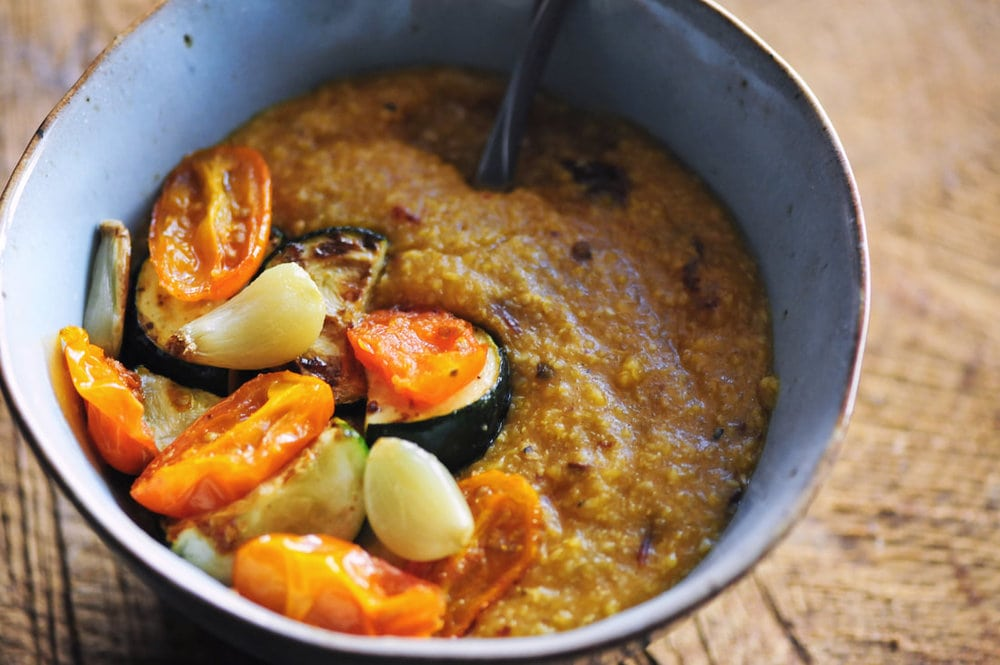 A warm, hearty, and nourishing bowl of grits (polenta) chock full of pumpkin, chipotle peppers, and sharp cheddar cheese. This beautiful gluten-free vegetarian dish is topped off with tender and nutritious garlic roasted vegetables. A perfect autumn meal! #grits #pumpkin #pumpkingrits #pumpkinchipotle #cheesy #polenta #garlic #roastedveggies #autumn #halloween #brunch