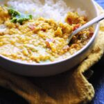 a white bowl with orange vegan dal and white rice on a yellow napkin cookie sheet background