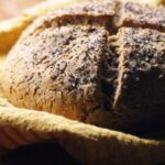 a boule of gluten free artisan bread topped with seeds