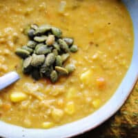 a large bowl of vegan corn chowder topped with pumpkin seeds