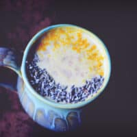 a teal mug on a dark background filled with cherry lavender moon milk topped with lavender buds and turmeric for contrast