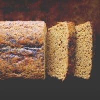 a top view of a gluten free lemon poppy seed bread made with chickpea flour on a dark backgroun
