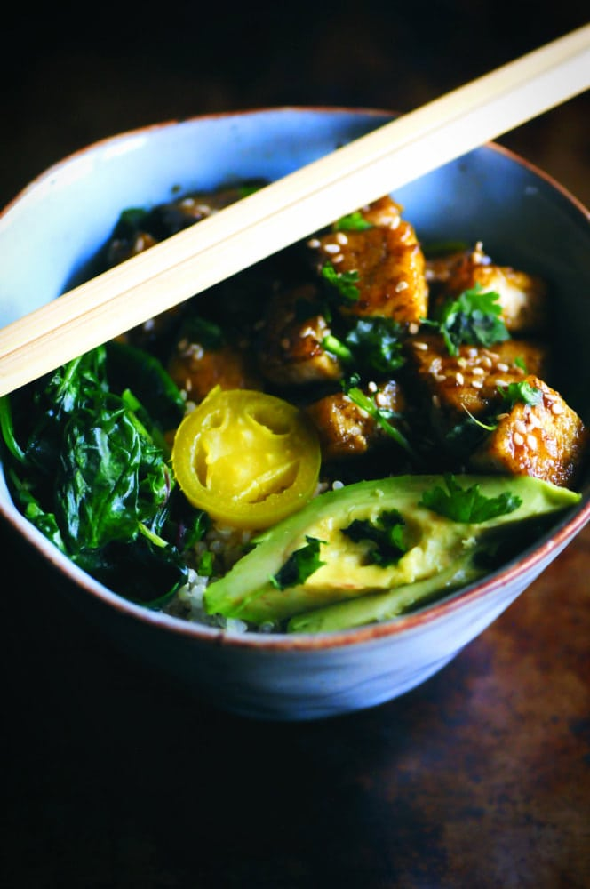 A beautiful vibrant green power bowl filled with quinoa, sweet and spicy tofu, mixed wilted greens, jalapeño slices, avocado, cilantro and sesame seeds. This makes an absolutely delicious vegan and gluten-free high protein lunch or dinner! #sweetandspicytofu #buddhabowl #quinoabowl #vegandinner #tofubowl #sweetandspicy #glutenfreelunch