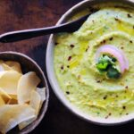 a white bowl filled with green avocado hummus alongside cassava chips