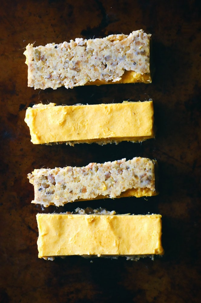 These date-free Vegan & Gluten-Free Mango Nice Cream Bars make for one easy, healthy, delicious, and refreshing frozen treat! A creamy frozen mango banana ice cream filling sits atop a chewy cardamom almond crust in this delightful dessert. #veganicecreambars #nicecream #nicecreambars #rawbars #veganbars #mangobars #mangonicecream #glutenfreeicecreambars