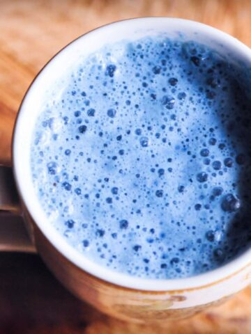 a white mug with blue moon milk inside on wooden backdrop
