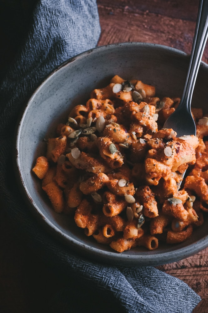 This gluten-free and vegan pasta dish is bursting with flavorful roasted red peppers, ground chipotle pepper and its secret ingredient of pumpkin seed milk! Topped off with pepitas, cilantro, red chili flakes and nutritional yeast, it makes for one big, spicy and delicious bowl of healthy comfort food. #pumpkinseedmilk #spicypasta #chipotlepasta #roastedredpeppersauce #glutenfreepasta #veganpasta #vegancomfortfood #pepitas