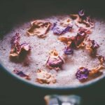 a close up of rose petals resting on a chai latte
