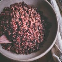 a top view of a big white bowl filled with cooked red quinoa
