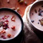 two mugs of seed cycling moon milk topped with rose petals lavender and seeds