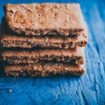 a stack of gluten free graham crackers on blue backdrop