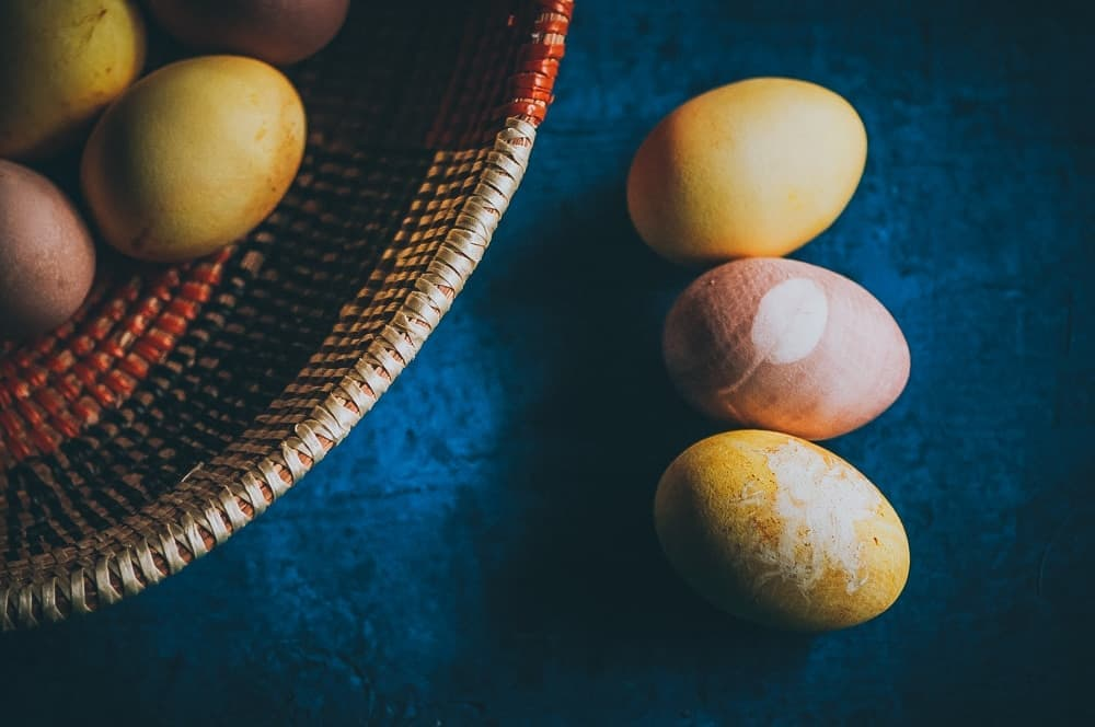 naturally dyed easter eggs on a blue wooden backdrop