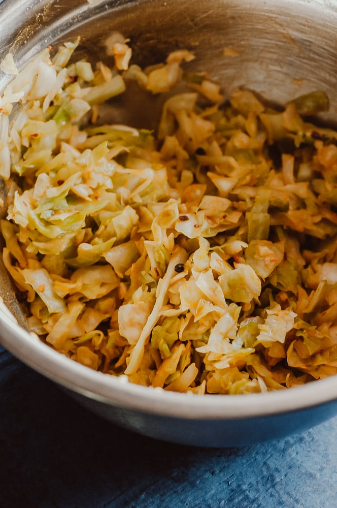 This probiotic rich Spicy Sauerkraut recipe with turmeric, red chili flakes, and black peppercorns is bursting with flavor and anti-inflammatory + gut health benefits! Easy, healthy, vegan, gluten-free and DELICIOUS! Learn all about how to make sauerkraut, health benefits, and more in this informative recipe post! #turmericsauerkraut #spicysauerkraut #howtomakesauerkraut