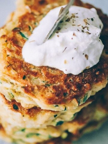 a stack of vegan zucchini fritters topped with a dollop of vegan sour cream