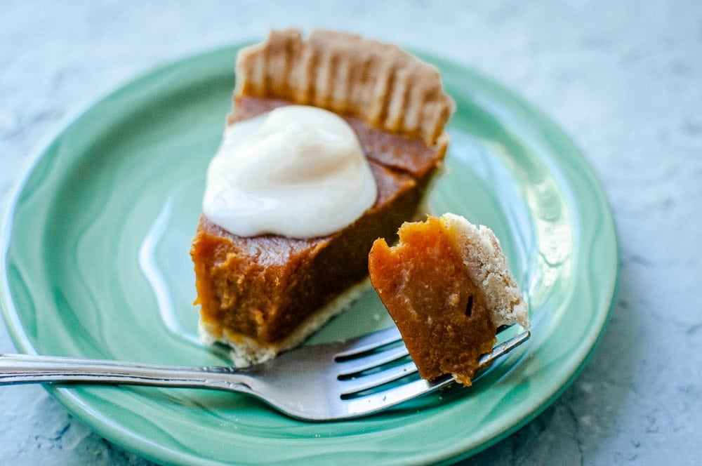 a slice of vegan gluten free pumpkin pie with coconut cream