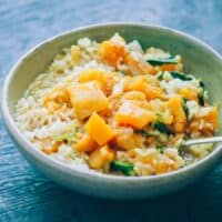 butternut squash curry in a white bowl served with rice