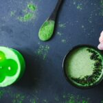 a green candle wooden spoon with moring powder black mug with green moringa moon milk all on a dark backdrop