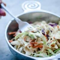 a pewter bowl filled with vegan coleslaw