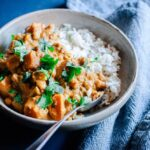 a white bowl filled with sweet potato curry on blue backdrop