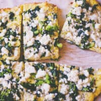a close up of a sliced keto coconut flour pizza topped with greens and feta cheese