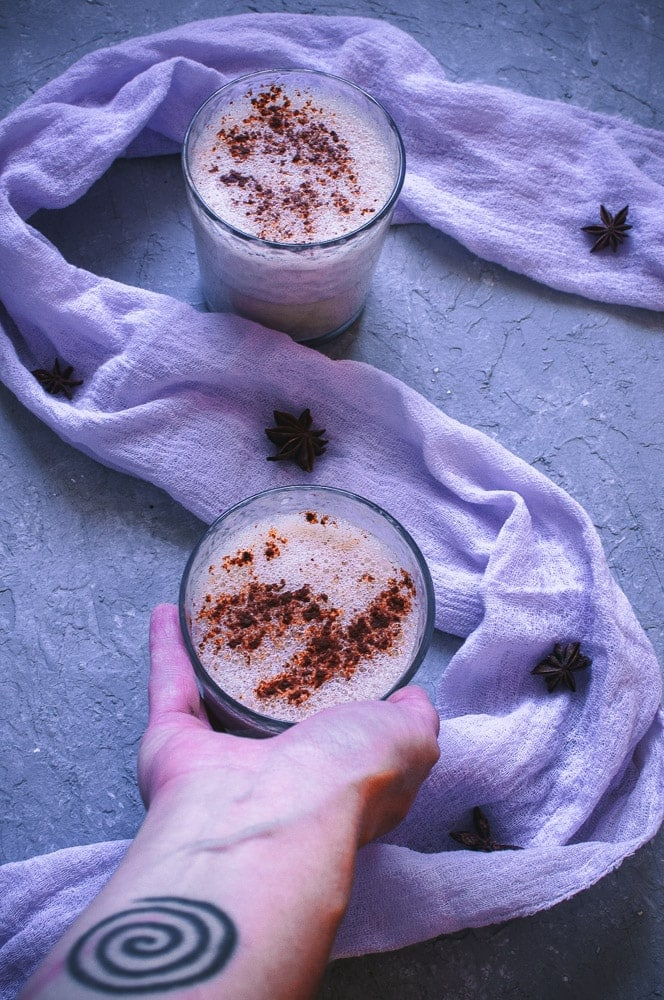 an image of purple cloth on gray background with a hand holding a cup of eggnog