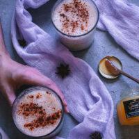 image of a hand holding a glass of eggnog next to a lavender colored gauzy cloth and a jar of cbd honey