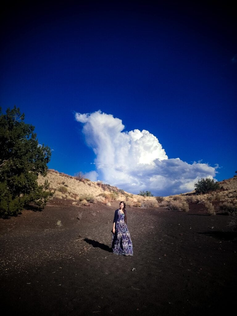 a woman in a dress standing in the desert beneath a large cloud in sky