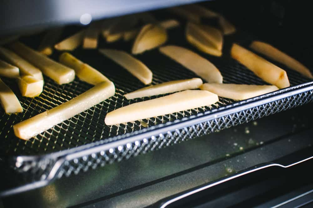 a close up image of french fries on the tray of cosori air fryer toaster oven