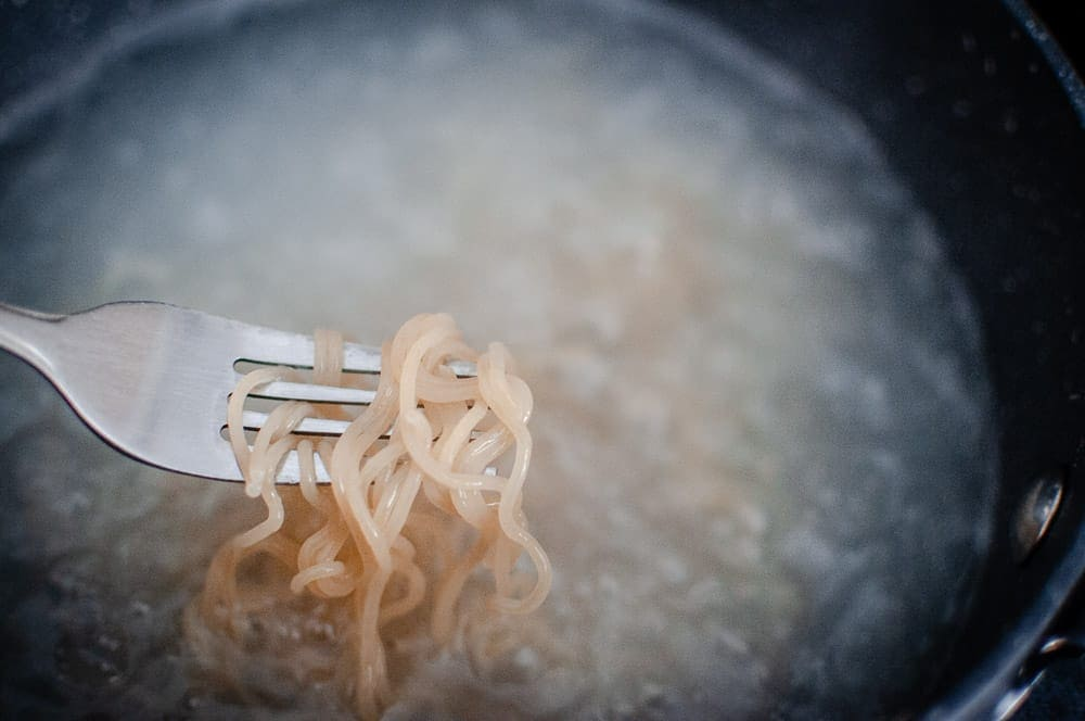 a close up shot of ramen noodles wrapped around a fork