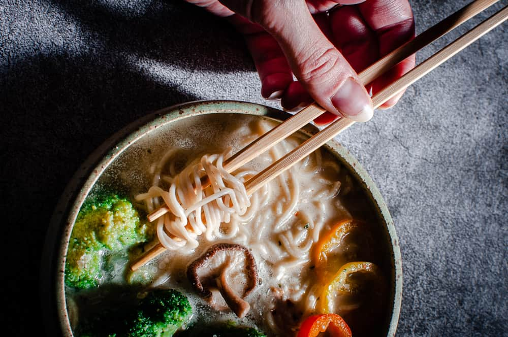 vegan ramen noodles in white bowl on gray background with a hand holding chopsticks