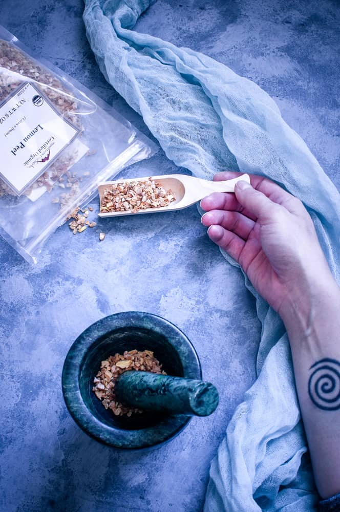 a top view flat lay of mountain rose herbs lemon peel spilled out next to mortar and pestle and arm with spiral tattoo holding wooden scoop