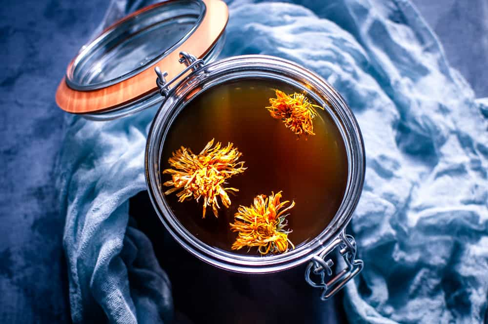 top view of open glass jar filled with mushroom broth topped with calendula flowers