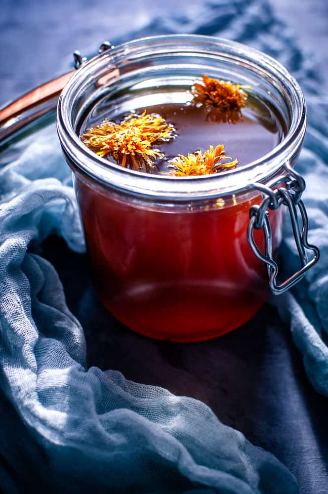 a clear glass jar filled with red vegan mushroom broth topped with calendula flowers