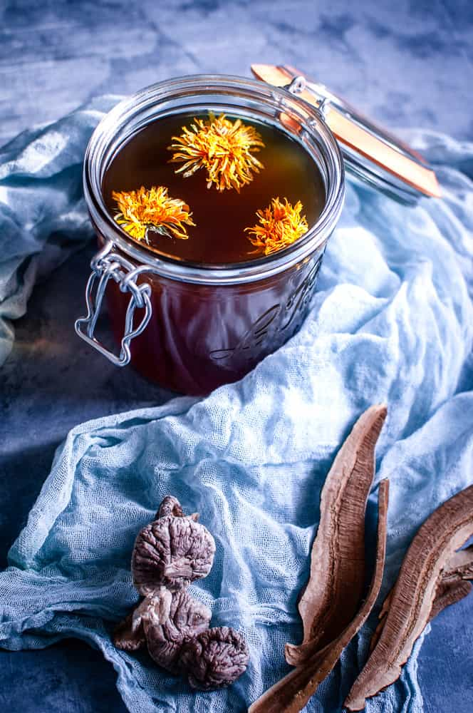 a clear jar filled with mushroom broth topped with edible flowers with mushrooms in the foreground on a sage gauze cheesecloth
