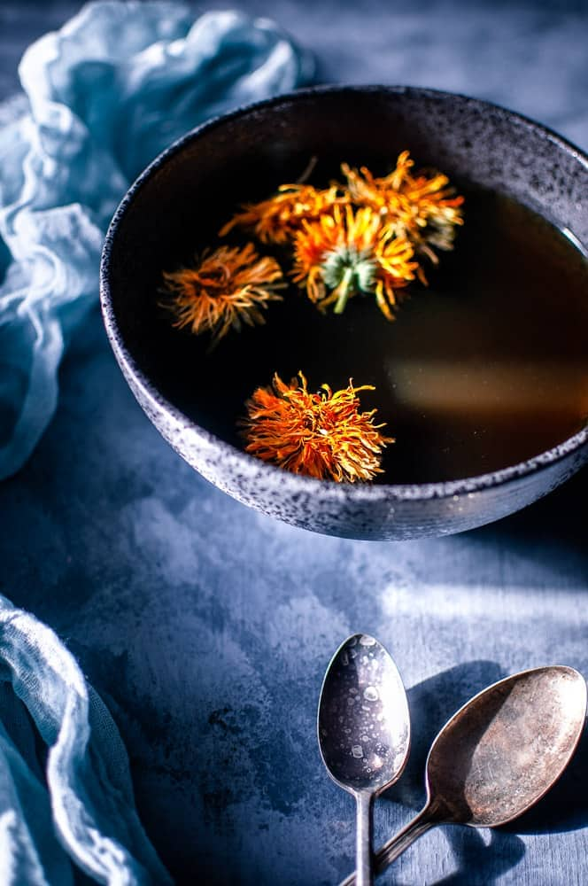 a gray backdrop with a black bowl filled with mushroom broth topped with calendula flowers alongside vintage spoons