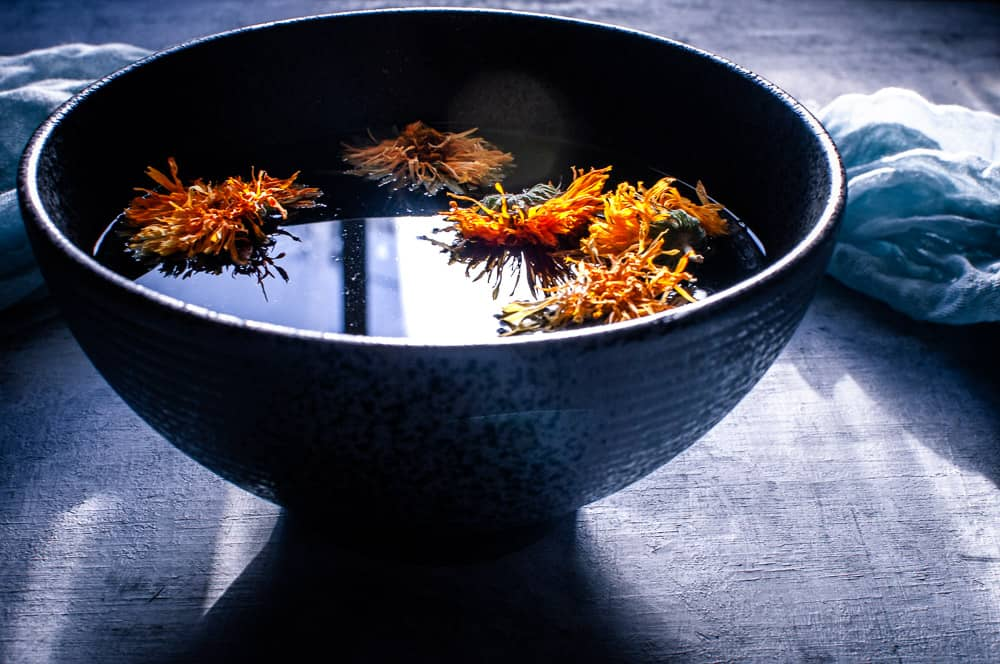 side shot view of black bowl filled with herbal broth topped with calendula flowers and the soft glow of light