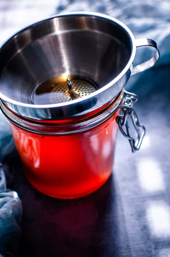 a jar filled with herbal broth with sunlight streaming through making it appear red