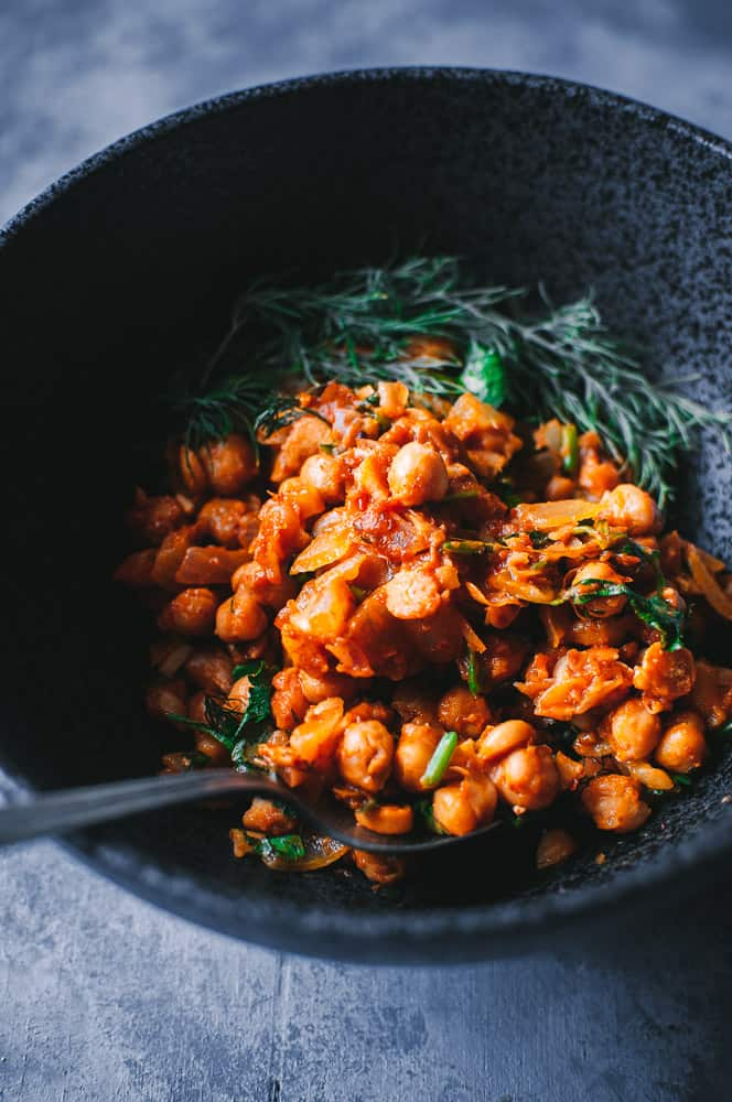 a black bowl filled with harissa chickpeas and a vintage spoon