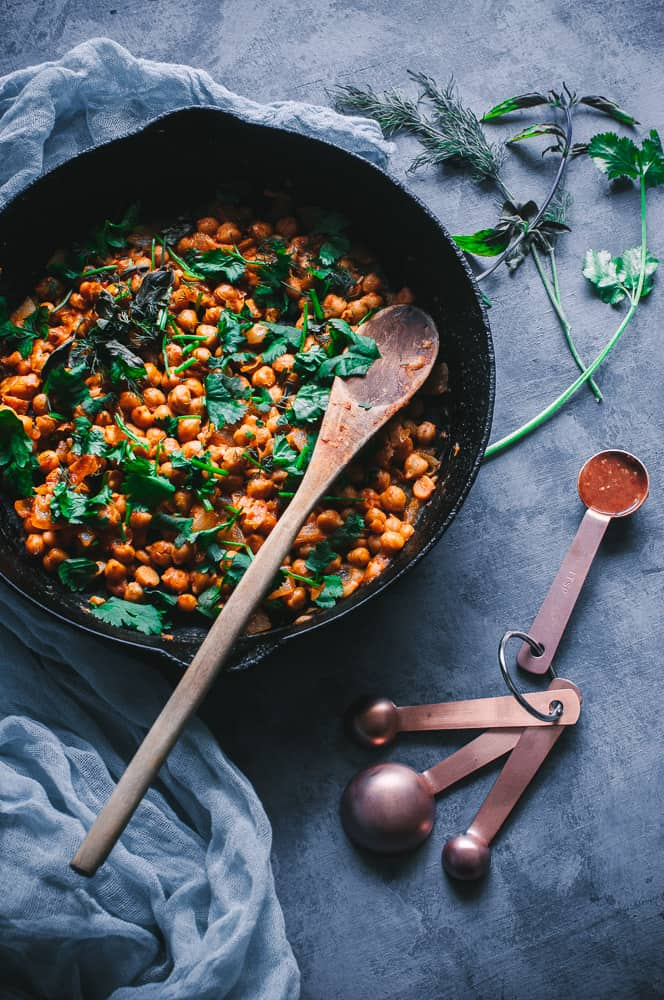 a cast iron skillet filled with orange harissa chickpeas topped with fresh herbs