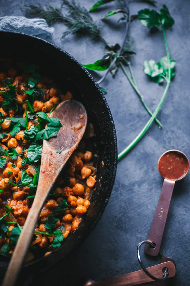a cast iron skillet filled with spicy chickpeas topped with fresh herbs alongside a measuring spoon filled with harissa sauce