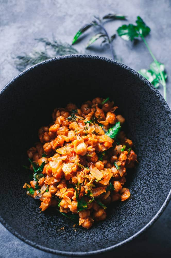 a black bowl filled with spicy moroccan chickpeas