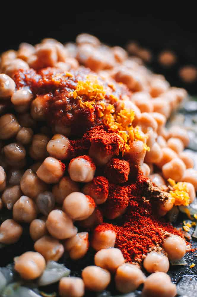 a mound of chickpeas topped with moroccan spices and orange zest