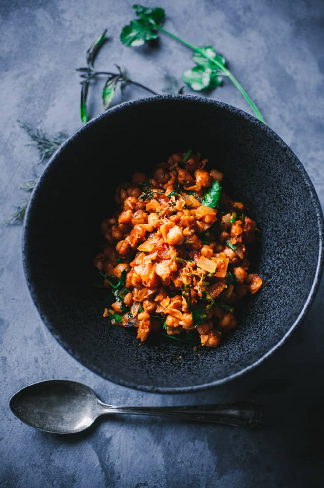a black bowl filled with moroccan chickpeas