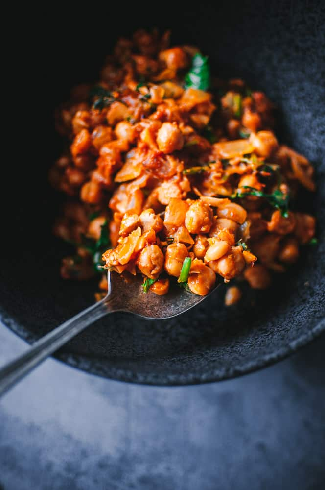 a close up of harissa chickpeas in black bowl with vintage spoon