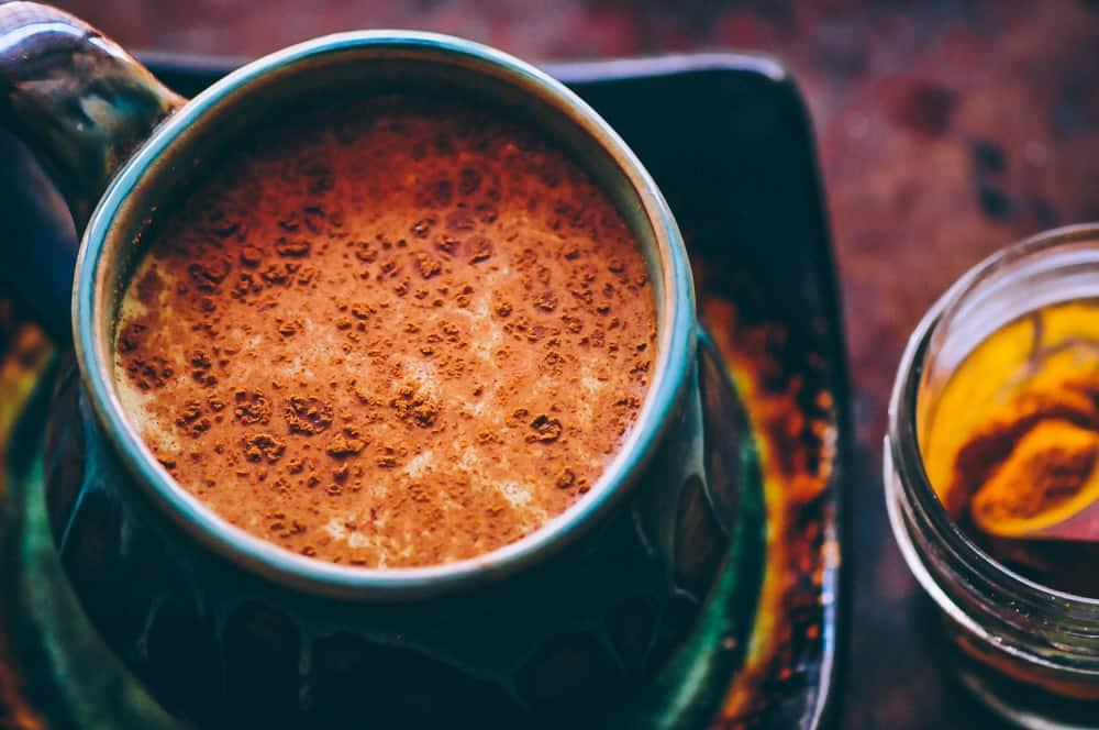 a mug of golden milk sprinkled with cinnamon