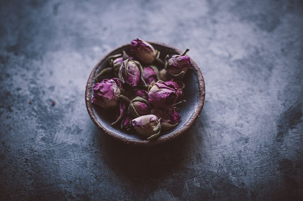 a shallow bowl filled with organic rose buds