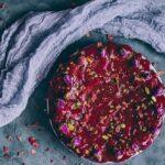 persian love cake with red glaze next to gauzy fabric